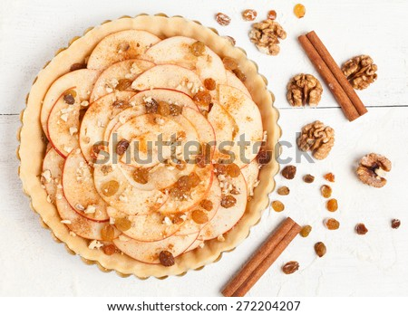 Homemade apple raw pie preparation. Tart with apples, raisins, nuts and cinnamon on white rustic kitchen table - stock photo