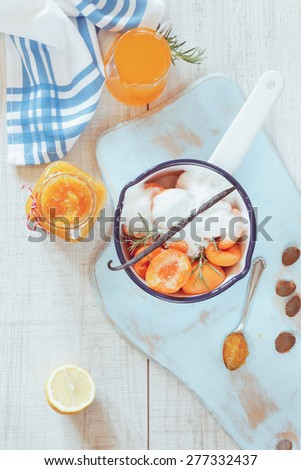Homemade apricot marmalade. High angle view of sugared apricots in a pan, preserving jar and apricot juice, rustic style,  on a wooden surface. Natural light  - stock photo