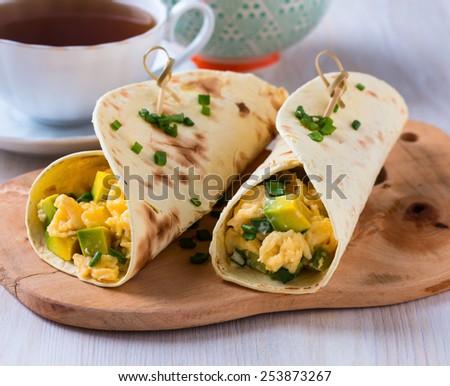 Homemade avocado scrambled egg wraps for healthy breakfast - stock photo