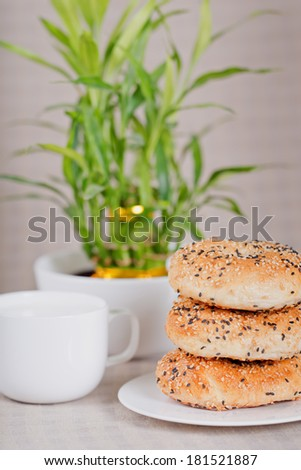 Homemade bagels with sesame seeds, cup of milk and bamboo background  - stock photo