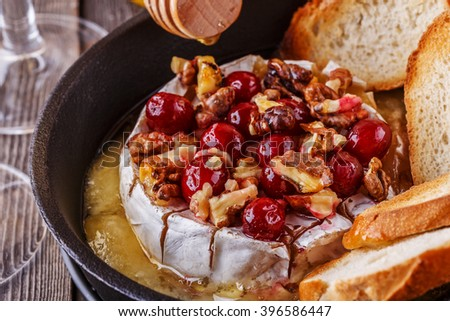 Homemade baked brie with honey, cranberry and walnut, selective focus. - stock photo