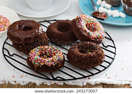 Homemade baked chocolate donuts with glaze and sprinkles - stock photo