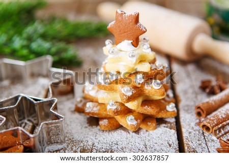 Homemade baked Christmas gingerbread tree on vintage wooden background. Anise, cinnamon, baking roll, star forms and decoration utensils. With icing sugar snow. Selfmade gift for xmas. - stock photo
