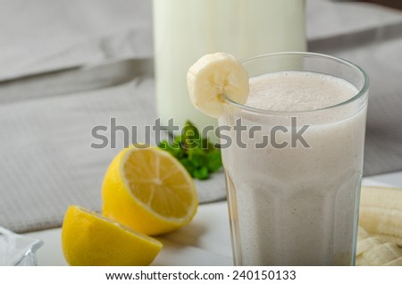 Homemade banana smoothie with lemons, herbs and organic milk from the farm - stock photo