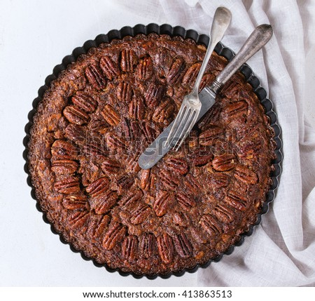 Homemade Big round caramel pecan pie in black iron forms, served with vintage cutlery on gray textile rag over white stone textured background. Flat lay. Square image - stock photo