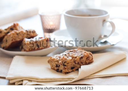 Homemade biscuits and a cup of tea on the table in the morning - stock photo