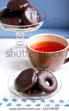 Homemade biscuits coated with chocolate and cup of tea - stock photo