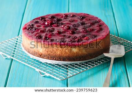 homemade blackberry cheesecake whole homemade blackberry cheesecake on turquoise wooden table - stock photo
