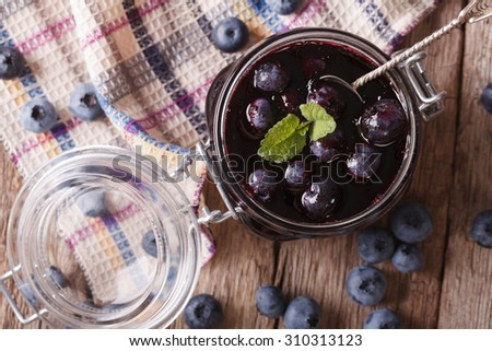 homemade blueberry jam in a glass jar close up on the table. horizontal top view - stock photo