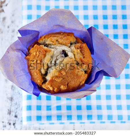 Homemade blueberry muffin wrapped in paper on blue checkered cloth. Top point of view  - stock photo