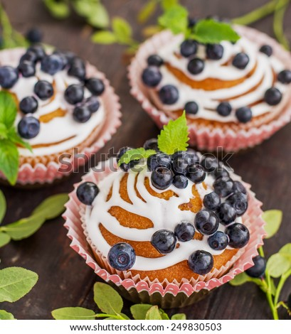 homemade blueberry muffins with icing and decorated with blueberries mint leaves on a wooden background with fresh blueberries forest branches. selective Focus - stock photo