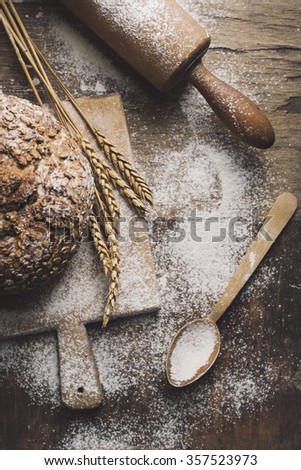 Homemade bread, flour, wheat ears and kitchen utensils on rustic table. - stock photo