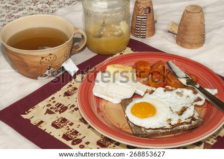 homemade breakfast, bread with butter, egg and cherry tomatoes - stock photo