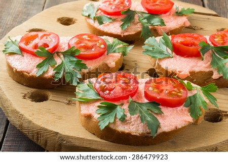 Homemade bruschetta with salmon butter, capelin caviar, cherry tomatoes and parsley on a rough wooden rustic board . Selective focus - stock photo