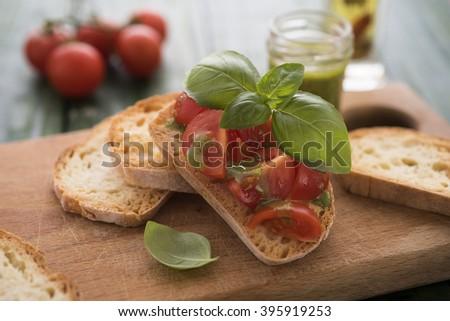 Homemade bruschetti with basil pesto and fresh tomatoes - stock photo