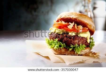 Homemade burger with delicious marinade and onion on silver countertop with copyspace - stock photo