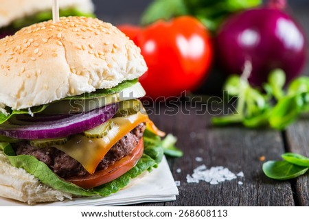 Homemade burger with vegetables on wooden table - stock photo