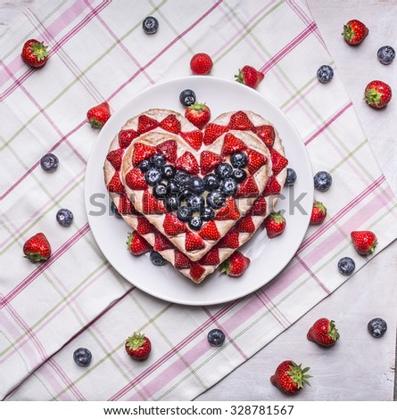 homemade cake In the form of heart  with blueberries and strawberries On a white plate on a background of a striped pink napkins with berries top view close up - stock photo