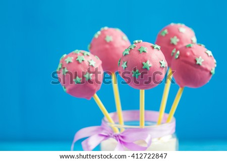 Homemade Cake pops with pink chocolate glaze, and green stars on a wooden background, selective focus - stock photo