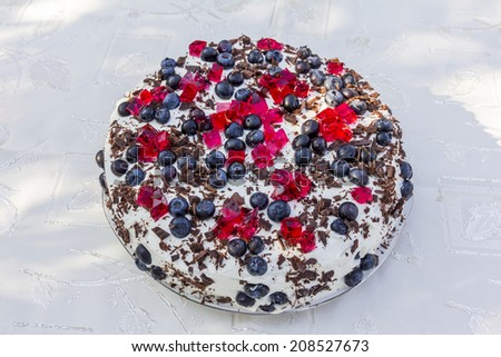 homemade cake topped with blueberries and pieces of red jelly on white tablecloth viewed from the top - stock photo