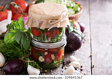 Homemade canned tomatoes with dill and garlic in jars - stock photo