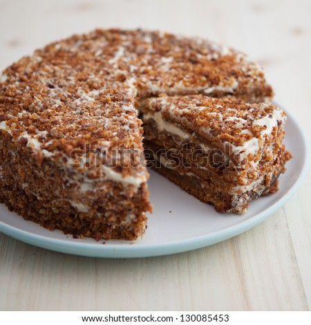 Homemade carrot and walnut cake with cut piece on a wooden table (square) - stock photo