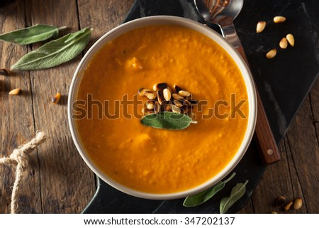 Homemade Carrot Ginger Soup with Toasted Pine Nuts - stock photo