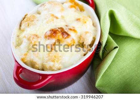Homemade cauliflower casserole  with cheese in a ceramic pot on rustic wooden table - stock photo