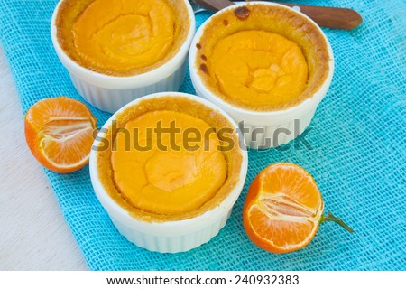 Homemade cheese cakes with tangerines in white ceramic moulds. Pieces of tangerines and dessert spoons on a sackcloth - stock photo