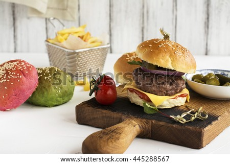 Homemade cheeseburgers, french fries and ingredients on kitchen table. Selective focus - stock photo