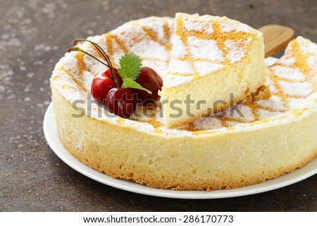 homemade cheesecake with powdered sugar and cherry on a white plate - stock photo