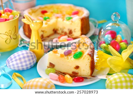 homemade cheesecake with raisins and egg shaped candies decoration on easter table - stock photo