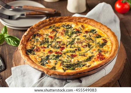 Homemade Cheesy Egg Quiche for Brunch with Spinach and Tomato - stock photo
