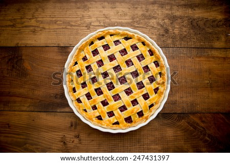 Homemade cherry pie on wooden table. Elevated view - stock photo