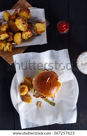 Homemade chicken burger with ketchup, beer and roasted potaoes on black wood background. Fresh fat dish for one person - stock photo