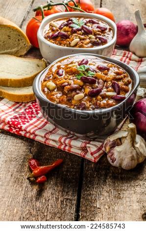 Homemade chilli con carne, bio bread and piri piri peppers - stock photo
