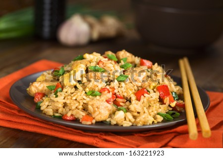 Homemade Chinese fried rice with vegetables, chicken and fried eggs served on a plate with chopsticks (Selective Focus, Focus one third into the dish) - stock photo