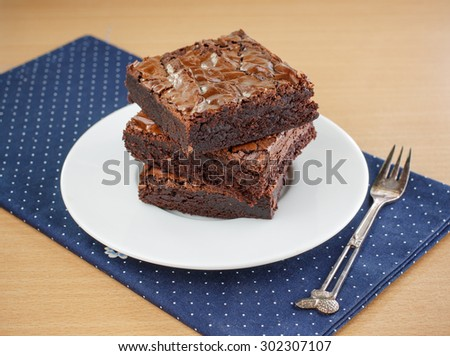 homemade chocolate brownie served on white plate. - stock photo