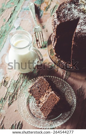 Homemade Chocolate Cake with Coconut Flakes and Dried Flower Decoration Next to a Glass Milk Jug on a Vintage Painted Wood Table. Moody Atmosphere - stock photo