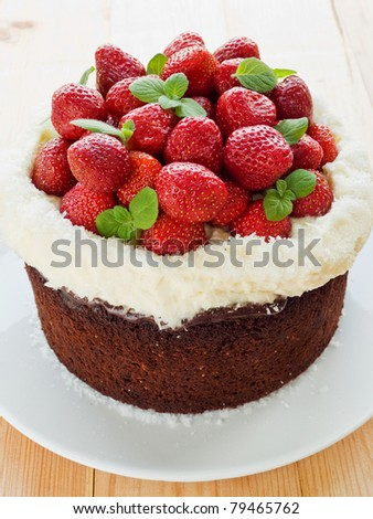 Homemade chocolate cake with strawberry, cream and mint. Shallow dof. - stock photo
