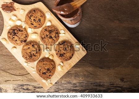 Homemade chocolate chip cookies and macadamia nut with melt chocolate serving wood platter; copy space for note or recipe  - stock photo