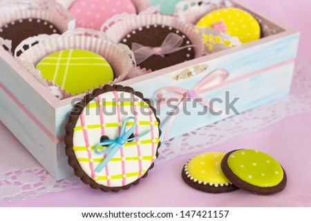 Homemade chocolate cookies decorated with royal icing.  Selective focus on left cookie with satin ribbon.  The wooden box is painted in light blue and decorated with pale pink satin ribbon  - stock photo