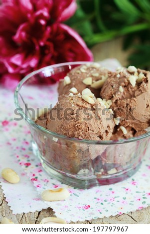 Homemade chocolate ice cream with peanut butter, sprinkle with chopped peanuts in a glass bowl on a wooden table. Selective focus - stock photo