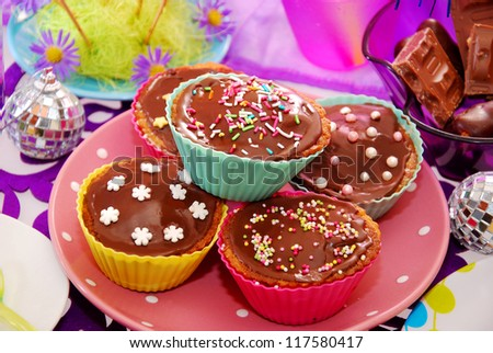 homemade chocolate muffins with colorful topping on birthday party table for child - stock photo