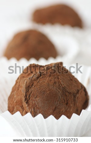 Homemade chocolate truffles with cocoa powder in white paper cups close-up. Shallow DOF. - stock photo