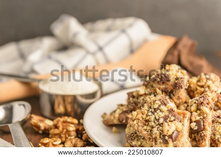Homemade chocolate walnut cookies with ingredients and kitchen utensils on a dark rustic wood table. - stock photo