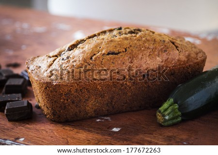 Homemade chocolate zucchini bread sitting on a wooden table with chocolate chunks and a zucchini - stock photo