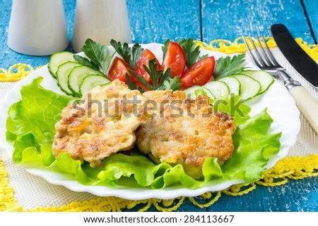 Homemade chopped cutlets, salad, tomatoes and cucumbers on a plate, cutlery, napkins with yellow trim on blue wooden background. Selective focus - stock photo