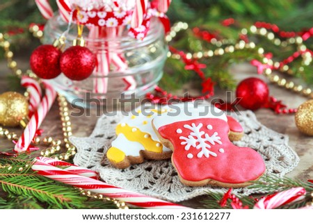 Homemade christmas gingerbreads  and red candy canes in the glass jar between Christmas decorations on wooden table, selective focus - stock photo