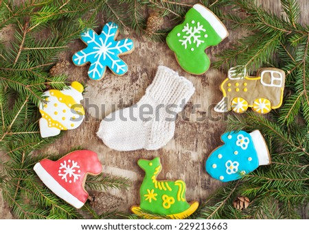 Homemade christmas gingerbreads painted as a horse, a hat and boot, locomotive, tree toy, snowflake and sock on the wooden background with fir branches. Selective focus and place for text. Toned - stock photo